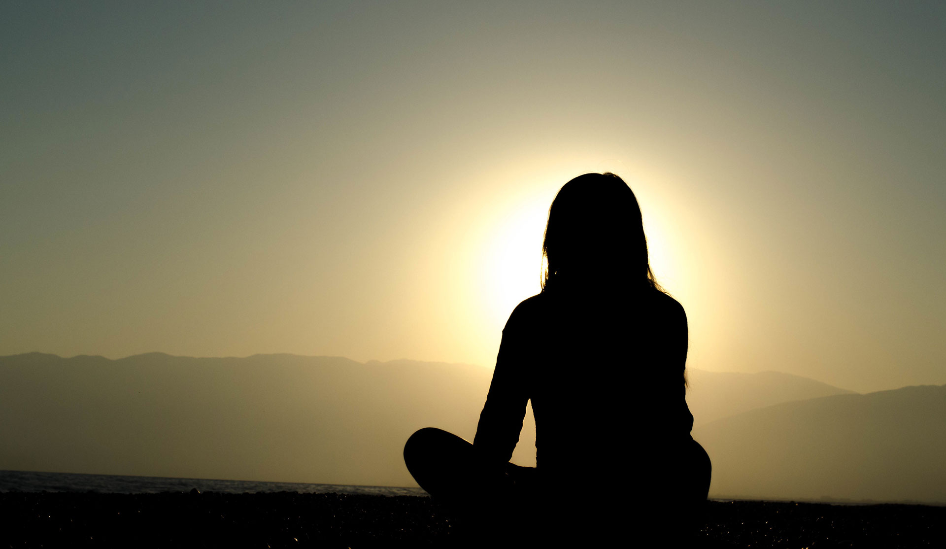 Silhouette of woman sitting on the ground in front of a sunrise